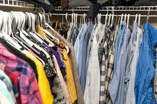 Male and female clothes arranged and hanging in a walk in closet