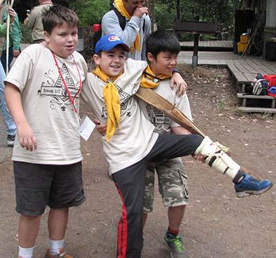 3 Scouts showing first aid skills for leg injury