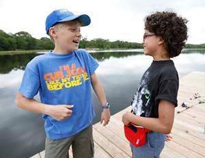 2 Cub Scout boys laughing on pier