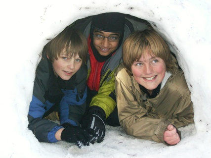 3 smiling Scouts BSA boys in a snow shelter
