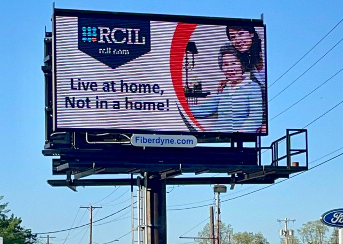 """The billboard pictured features NYAIL's ongoing campaign message, """"Live at home, not in a home!"""". At the top is RCIL's logo and website. To the right is a picture of two people, one older and one younger."""
