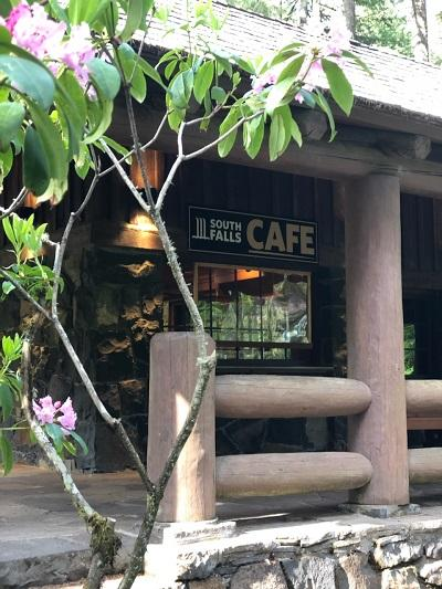 Photo of the front of Silver Falls Cafe with their new signage, stone exterior, hewed-log railings, and graceful rhododendron plants.