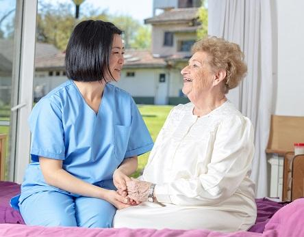 Image of smiling homecare worker in scrubs sitting next to senior woman on bed holding her hand. Pill bottle and window with neighborhood view in background.