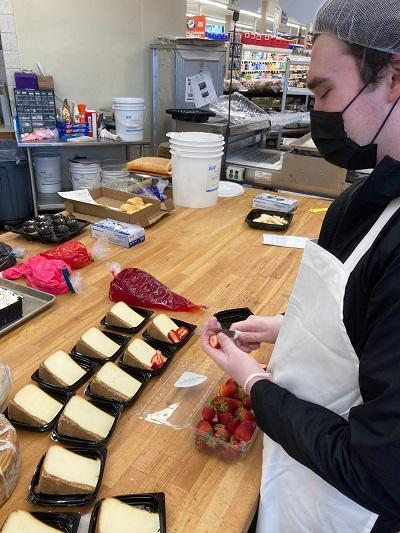 Photo of OCB client Kobe Hoover decorating cheesecake slices in Safeway bakery