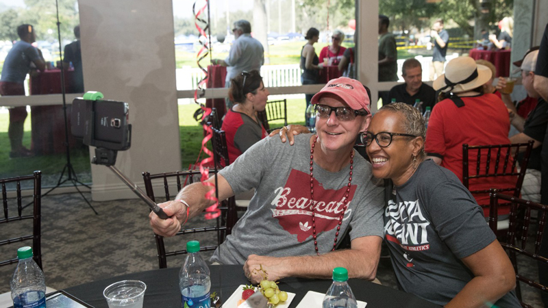 Two people share a selfie at a UC Alumni Association event.