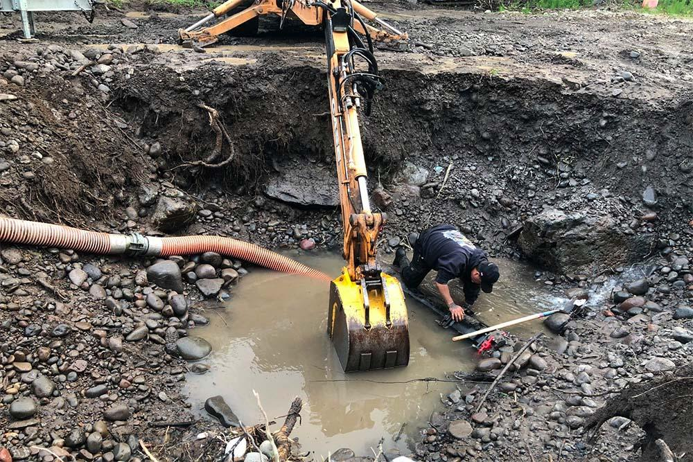Tribal staff work to repair Warm Springs' main water line. Photo from May 2019. (Warm Springs Facebook page)