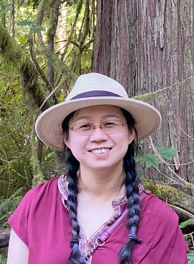 Image of a woman with two braids wearing a hat and glasses outside in front of a tree.