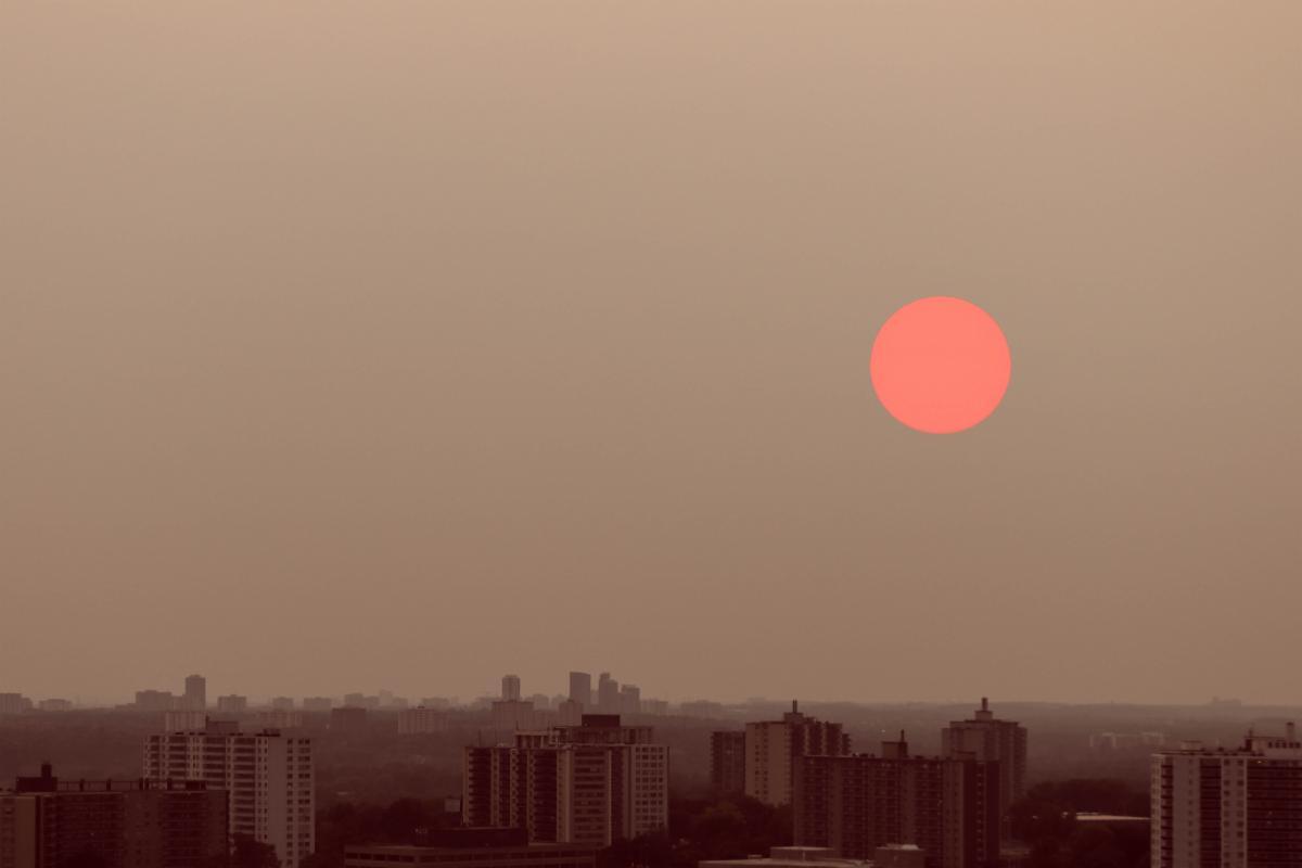 Image of city skyline with smoky sky and red sun.