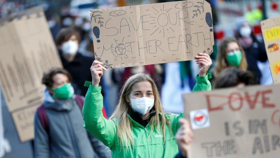 """Woman in a green jacket wearing a mask at a protest holds a sign that reads """"Save our mother earth!"""""""