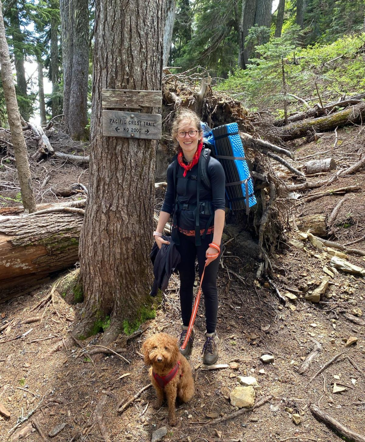 """Woman wearing glasses and backpacking gear stands in front of a sign that reads """"Pacific Crest Trail No 2000"""". She holds a leash with a medium brown dog."""